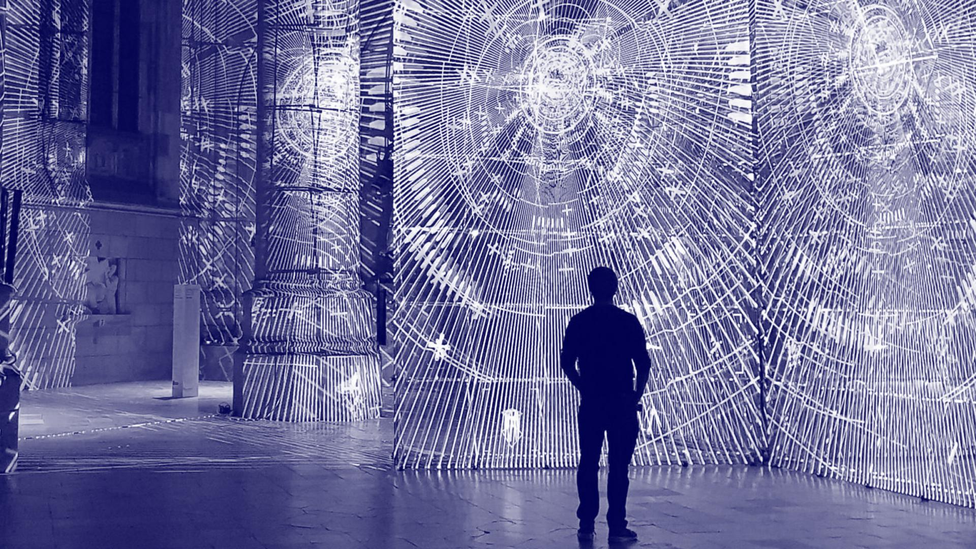 Zdjęcie przedstawia mężczyznę stojącego przed instalacją wizualną | The picture shows a man standing in front of a visual installation