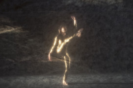 Zamazane, ciemne zdjęcie. Czarna scena, na której tańczy kobieta w złotym kombinezonie. | Blurred, dark photo. A black scene where a woman in a golden jumpsuit is dancing.