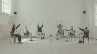Grupa osób, siedząca w okręgu i naśladująca gesty robota. | A group of people sitting in a circle imitating the robot's gestures.